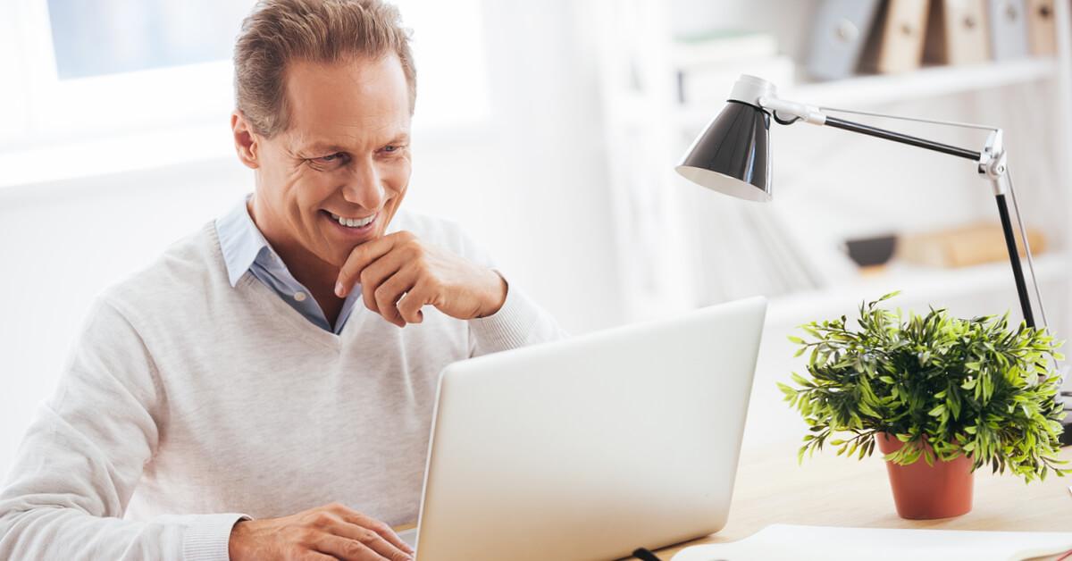 man-smiling-at-computer-screen