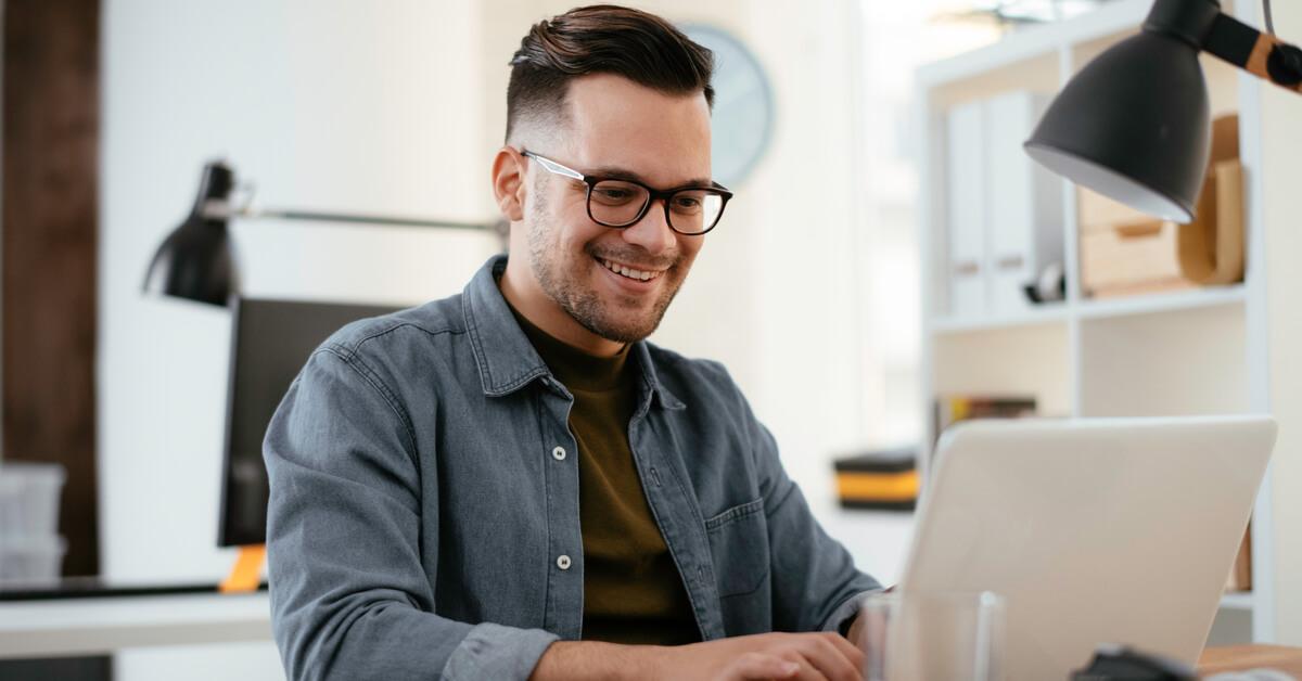 man-smiling-at-laptop-screen