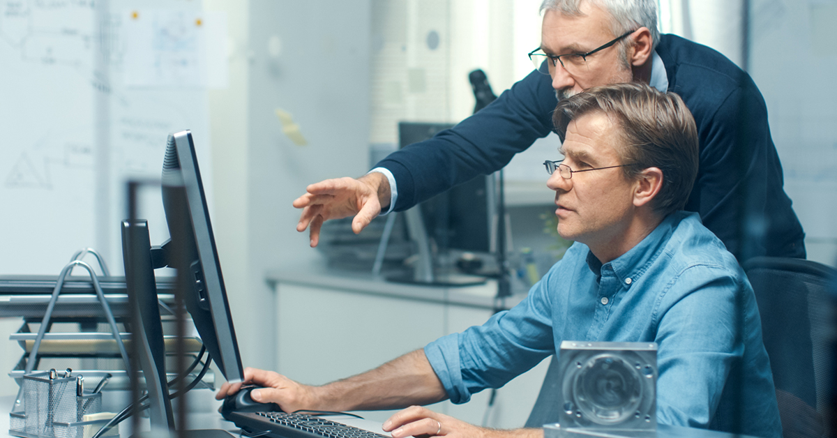 two men working at one computer